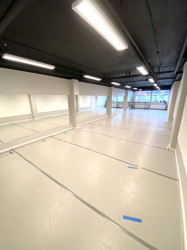 Balletskolen i Hørsholms balletstudie med dansevinyl, spejlvæg og løse barrer. Her er dejlig højt til loftet og vinduer med naturligt lysindfald.